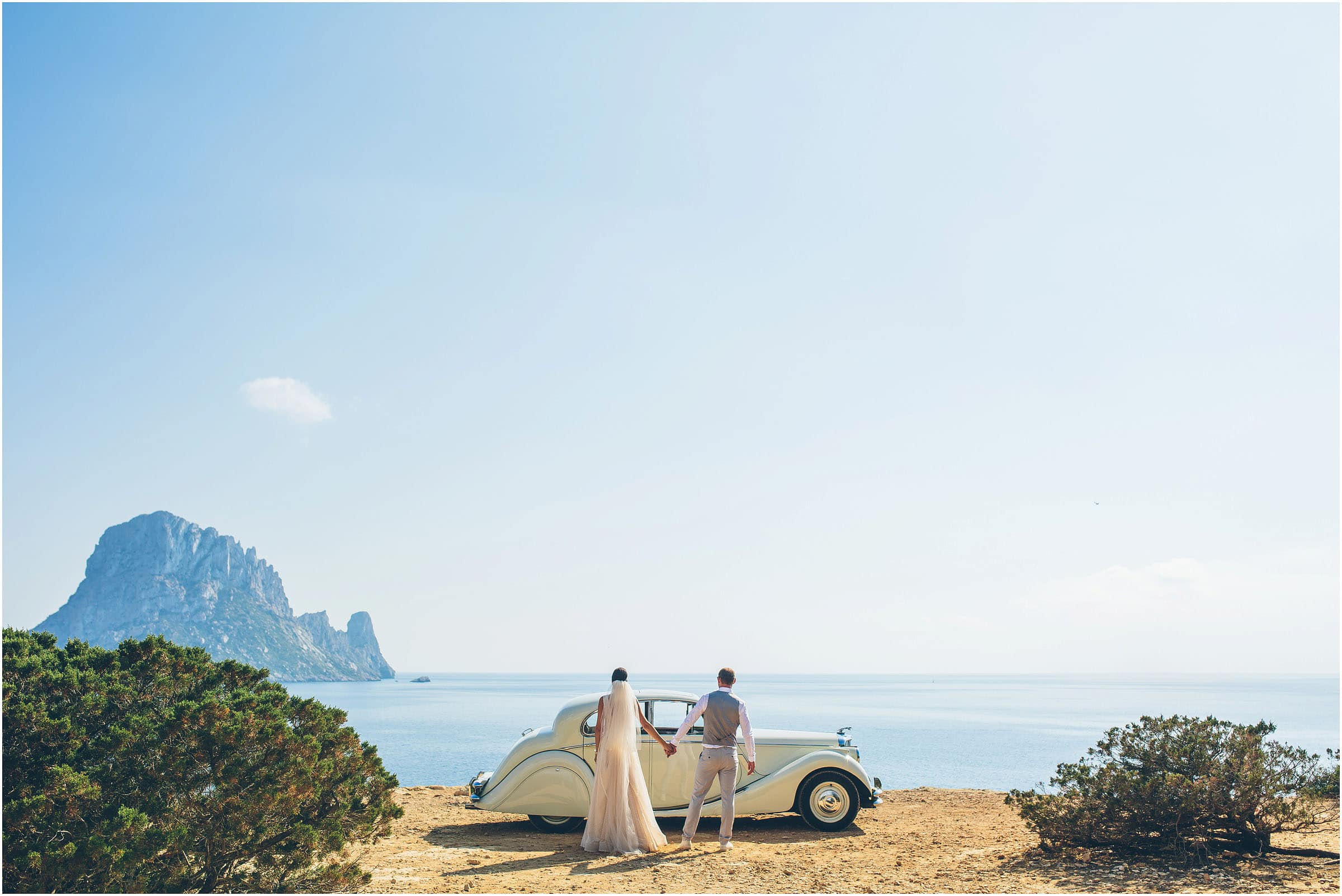 A couple on their destination wedding in Ibiza photographed standing on the beach in front of a classic car with the sea and a pale blue sky.