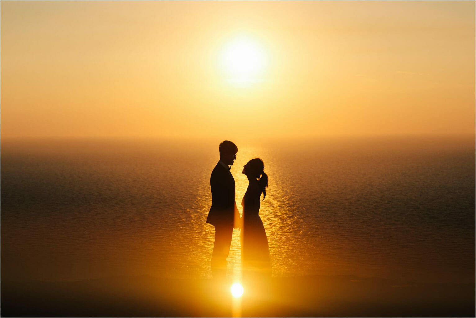a bride and groom at sunset in santorini
