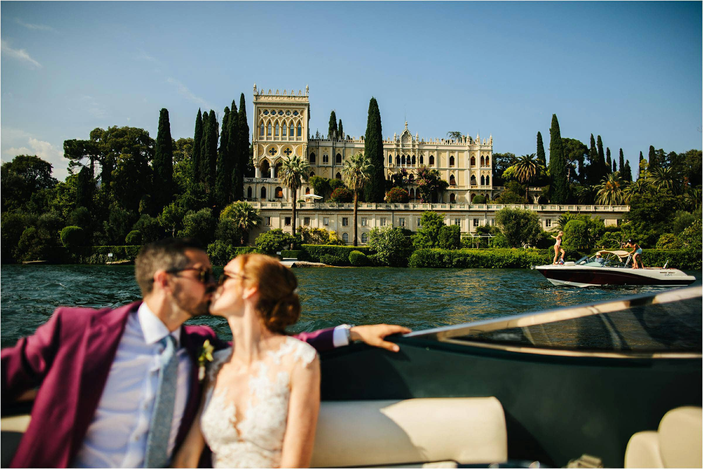 bride and groom in a Riva kissing in front of Isolators del Garda in Italy