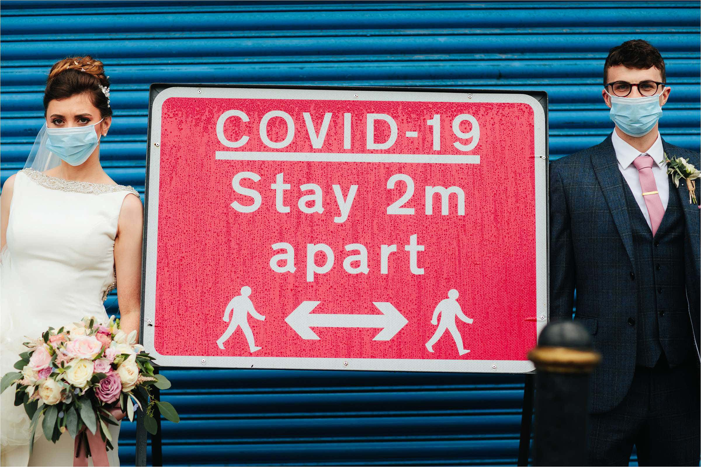 bride and groom standing against blue backdrop either side of covid-19 stay 2m part red sign