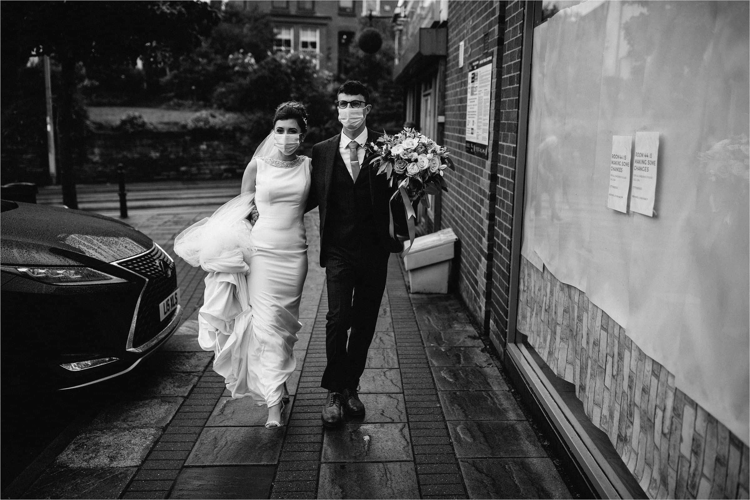 bride and groom walking arm in arm wearing face masks