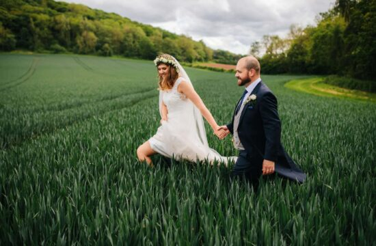 bride and groom walking hand in hand through a field at Brinsop Court